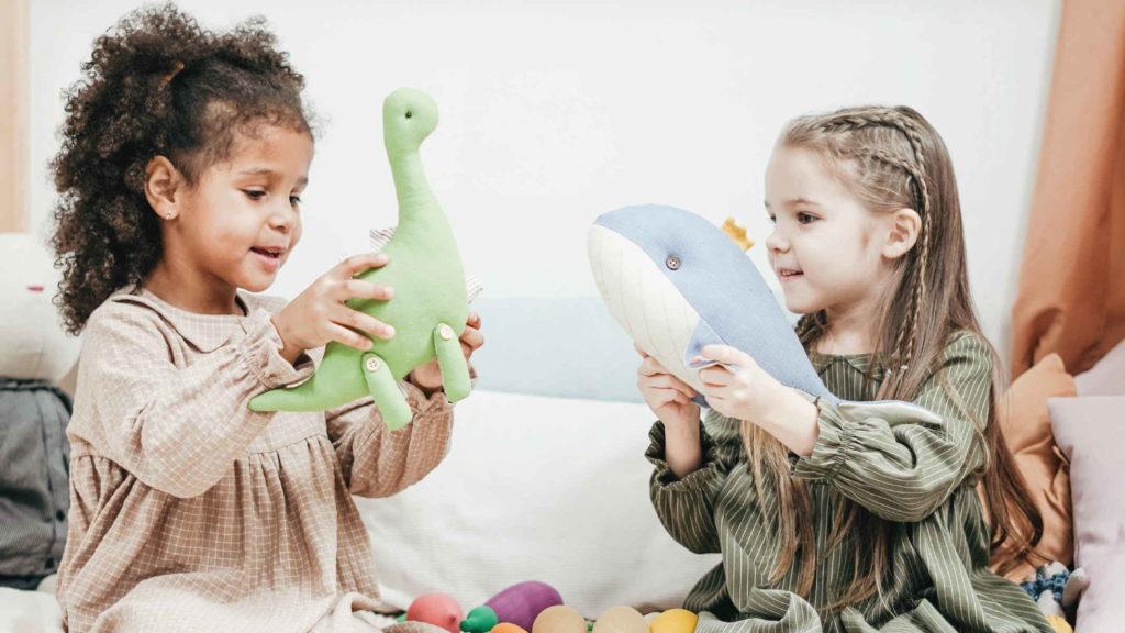 Две маленкьие девочки играют с мягкими игрушками