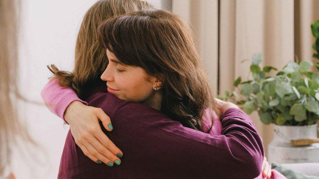 Две женщины обнимаются друг с другом