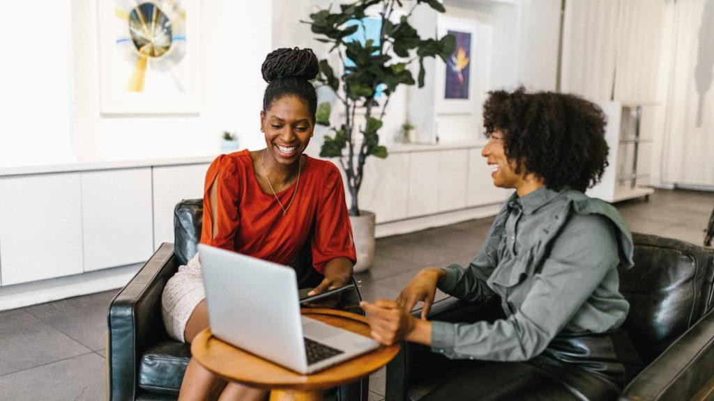 Две женщины работают за компьютером сидя на креслах