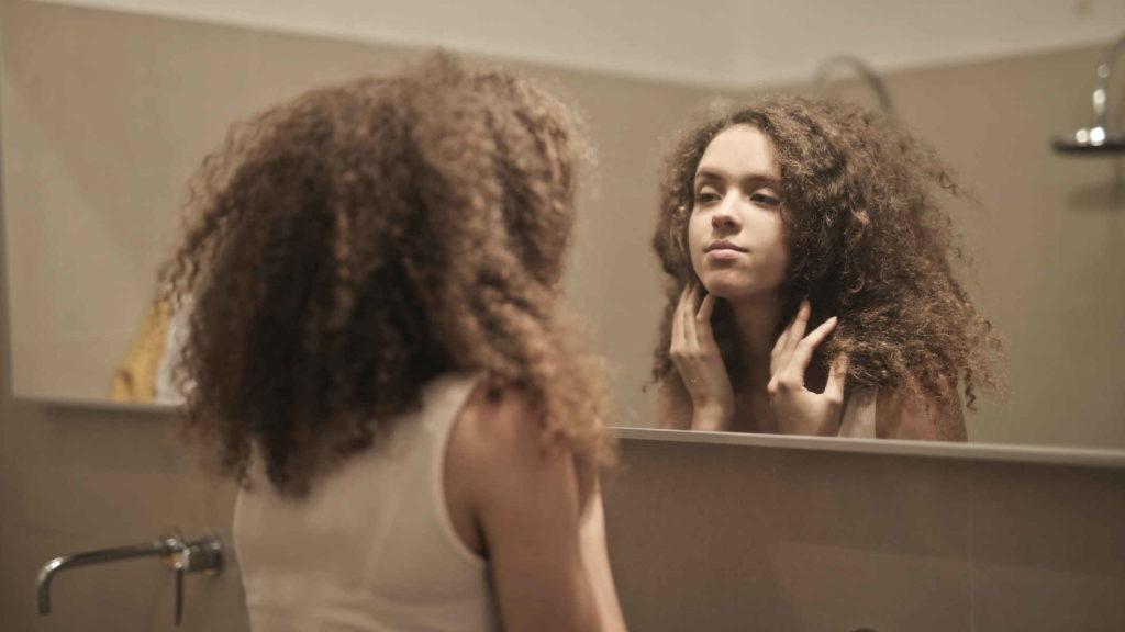 Кучерявая девушка смотрит в зеркало в ванной