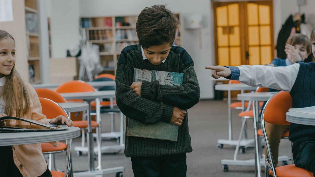Мальчик опустил голову и идет по классу