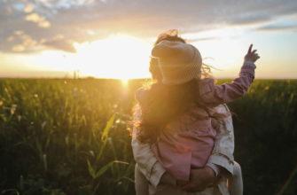Мать несет свою дочь на руках в поле