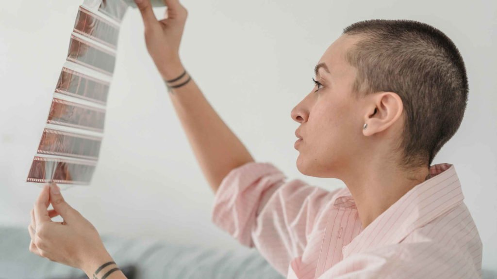 Молодая девушка рассматривает фотографии с пленки