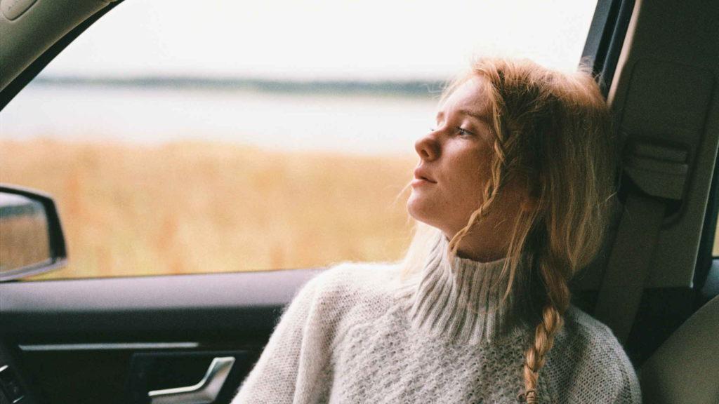 Молодая девушка в машине смотрит в окно