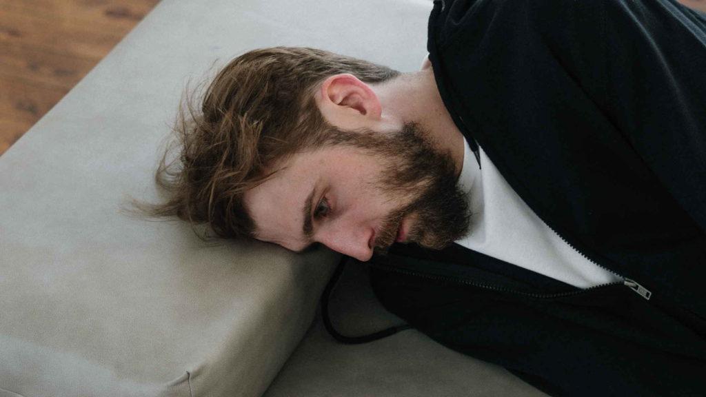 Мужчина психопат лежит на кушетке
