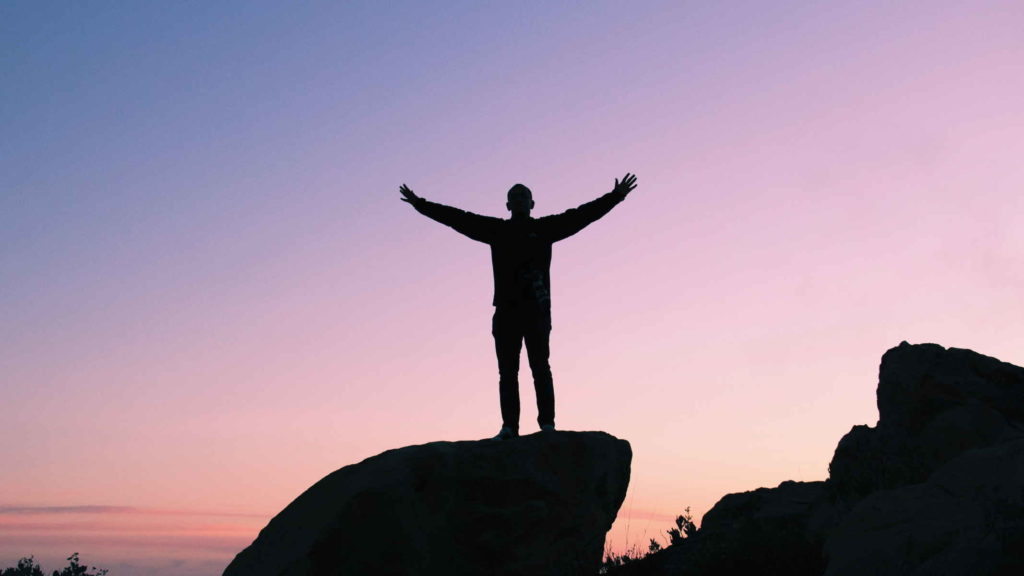 Мужчина стоит на горе на фоне лилового заката