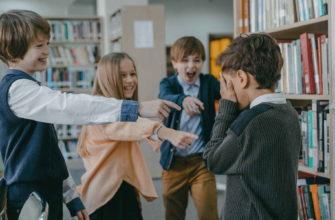 Одноклассники смеются над маленьким мальичком в библиотеке