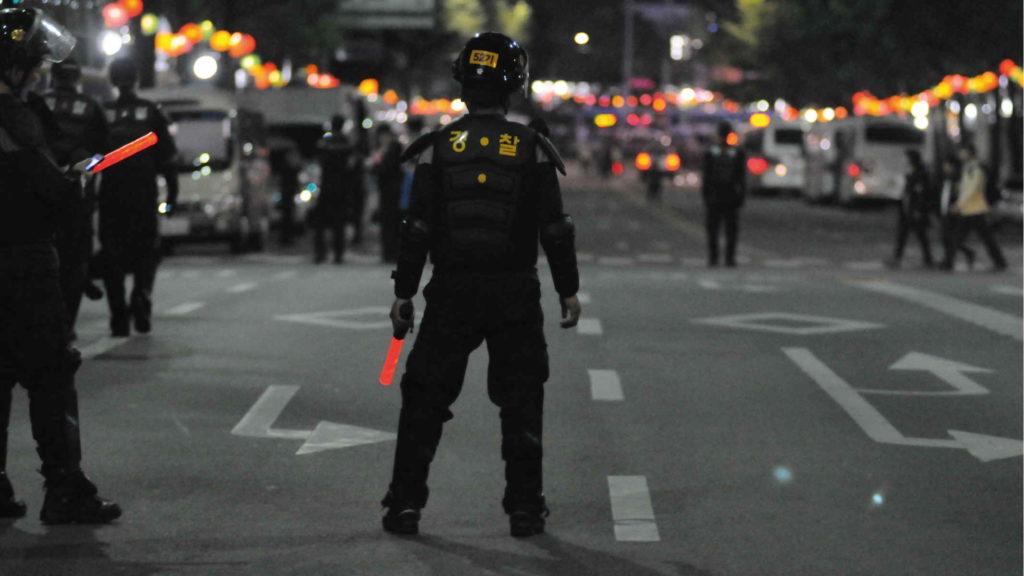 Полицейский стоит на площади в обмундировании