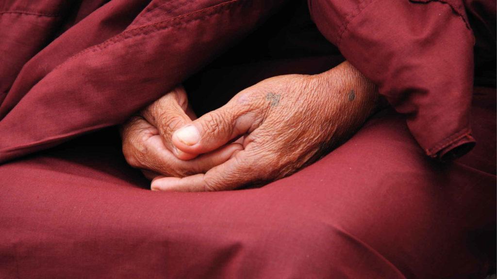 Руки пожилой женщины в красном балахоне