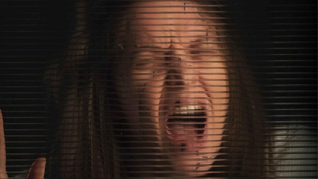 Женщина кричит через стекло