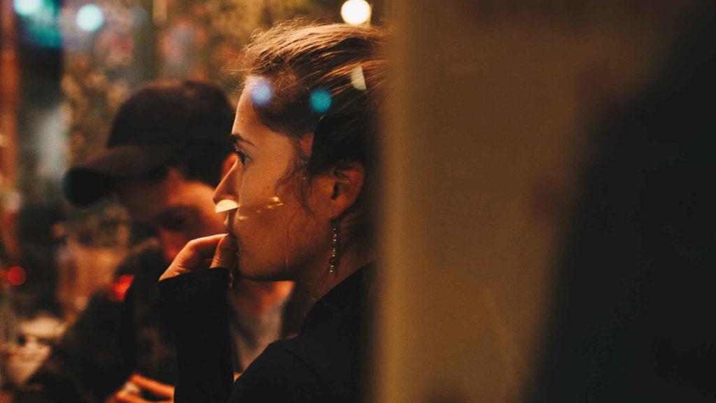 Женщина смотрит через стекло кафе