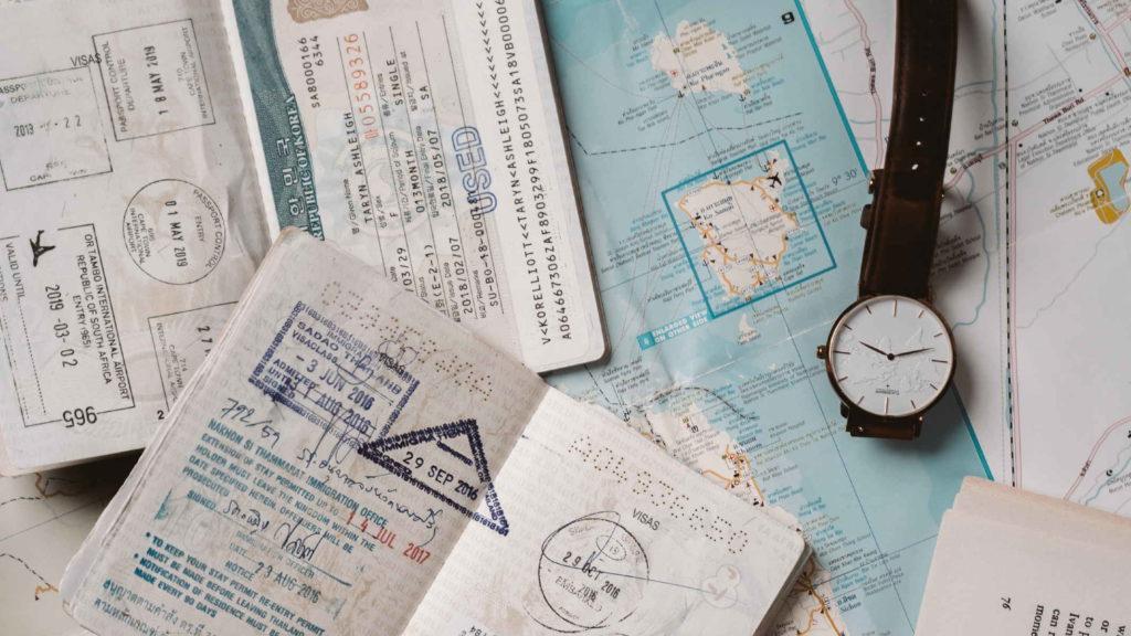 Часы лежат на карте рядом с паспортом