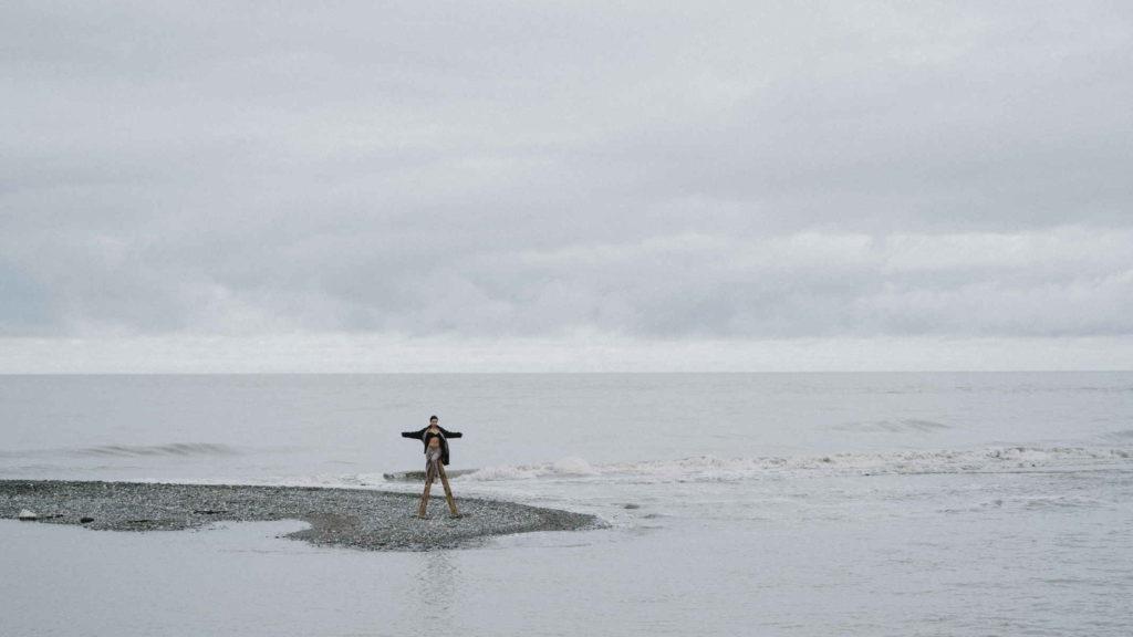 Человек стоит в далеке на фоне моря и пасмурного неба