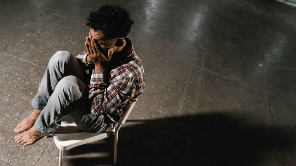 Человек в одиночестве сидит на стуле