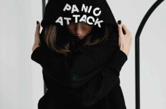 Девушка сидит в черной толстовке с надписью паническая аттака