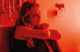 Девушка в красном освещении сидит грустная