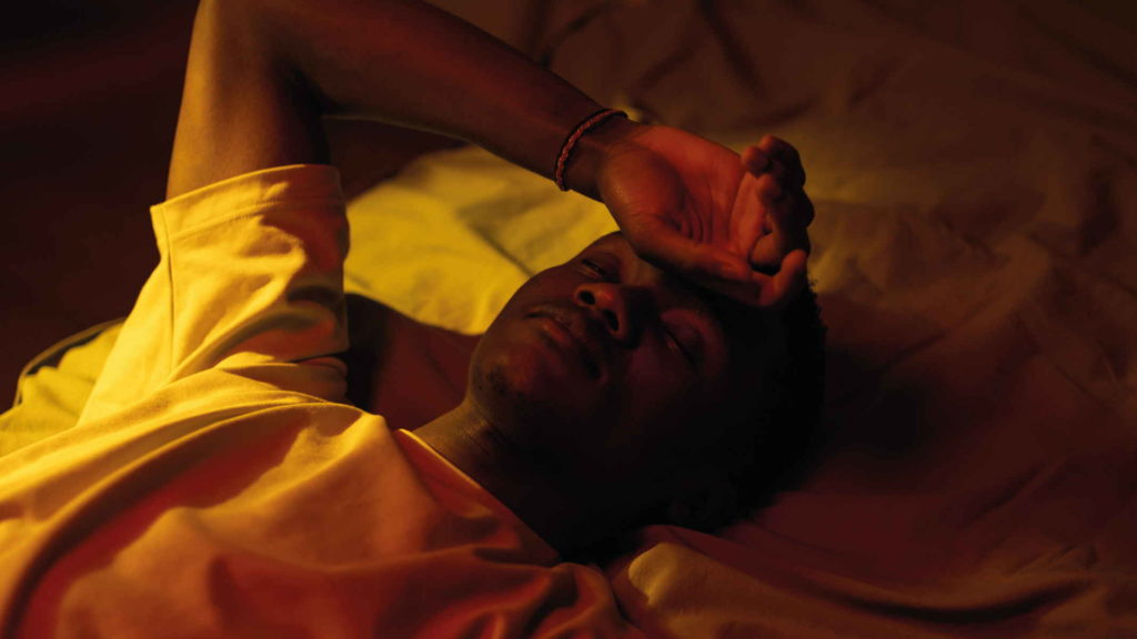 Грустный и задумчивый мужчина лежит на кровати