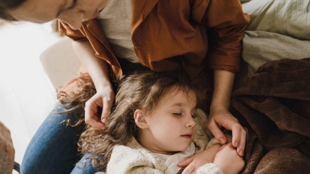 Маленькая девоча лежит на коленях матери