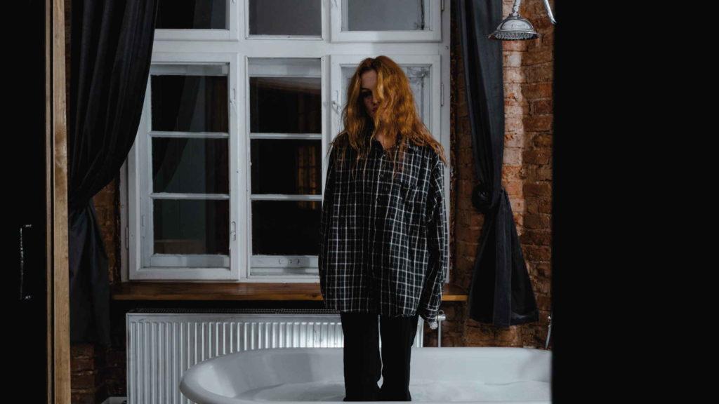 Молодая девушка стоит в ванной в подавленном состоянии