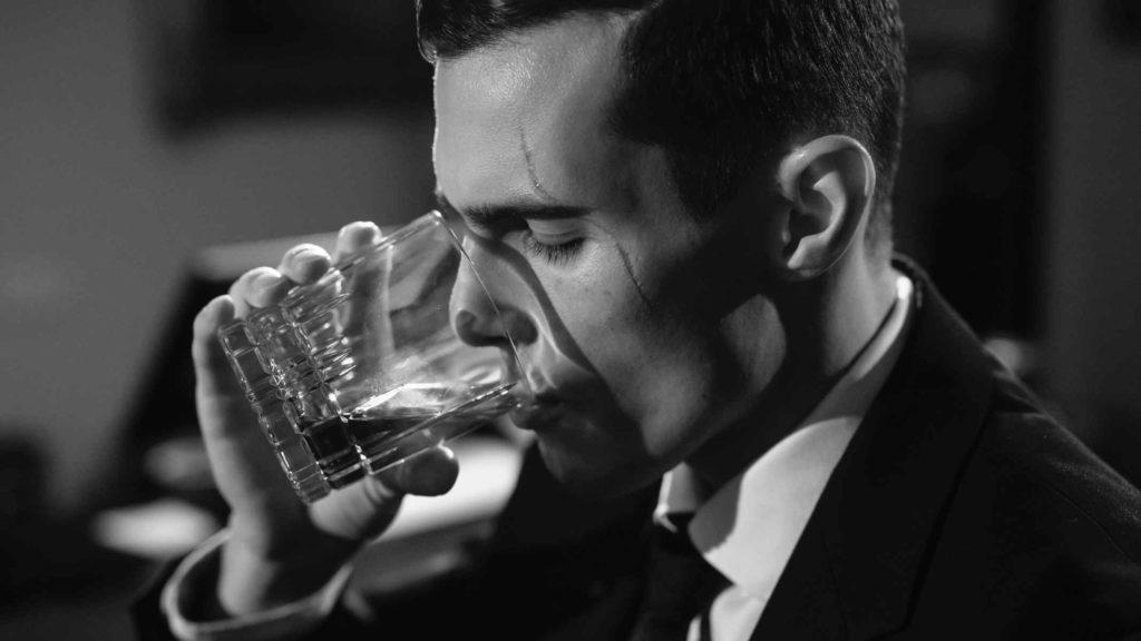 Мудчина пьет бокал с жидкостью