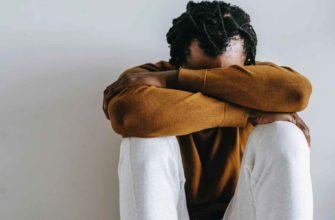 Мужчина сидит и грустит в белых штанах