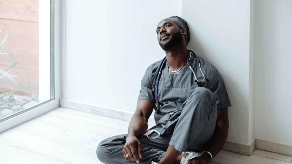 Мужчина устал работая врачом и сел на пол