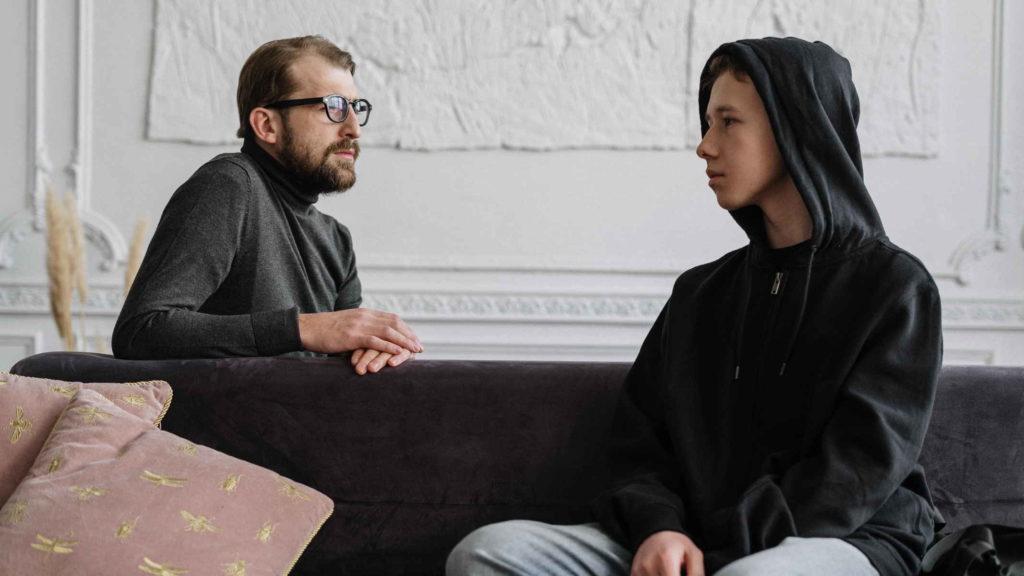 Психолог и подросток разговаривают сидя на диване