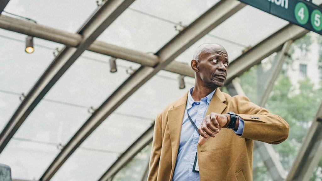 Пунктуальный взрослый мужчина смотрит на время