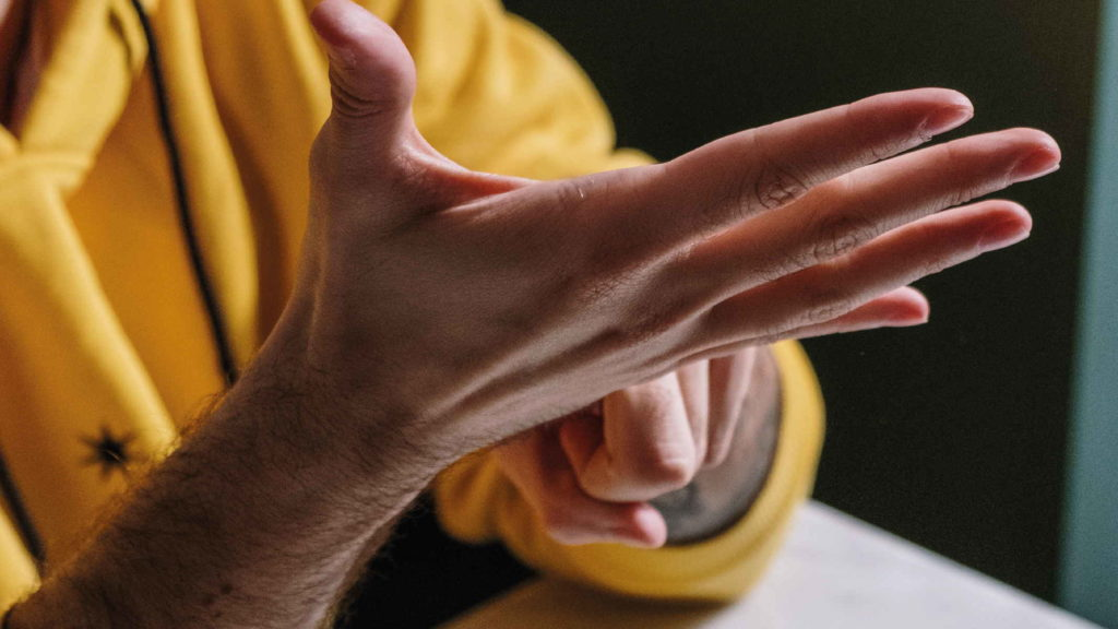 Рука мужчины в желтой кофте