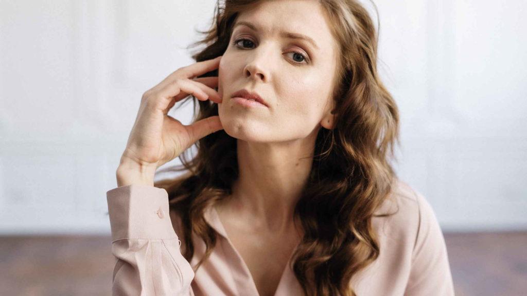 Женщина в розовой блузке задумчиво смотрит