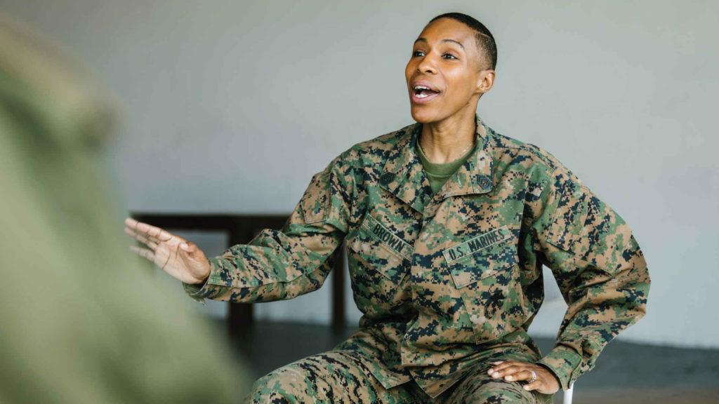 Женщина военная сидит и жестикулирует