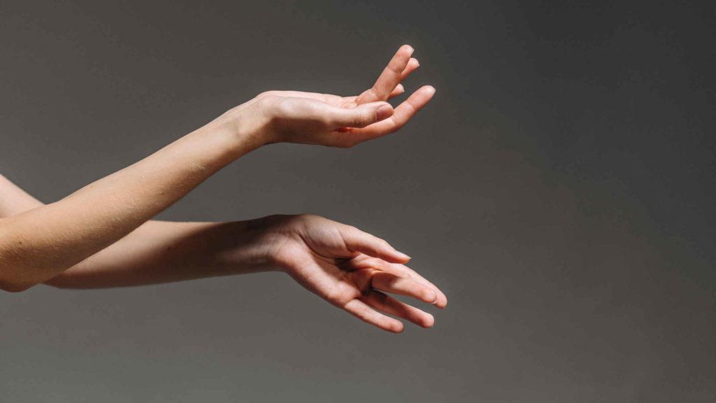 Женские руки на фоне серой стены