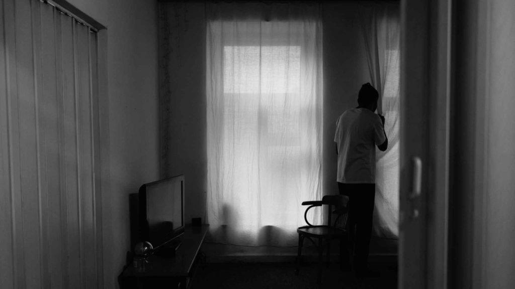 Человек смотрит в окно и боится преследования