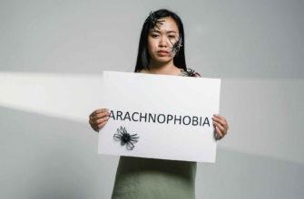Девушка держит в руках плакат арахнофобия