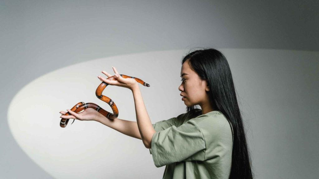 Девушка держит змею на руках