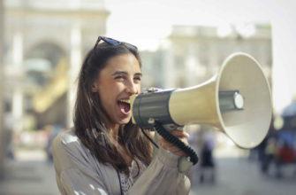 Девушка говорит в громкоговоритель