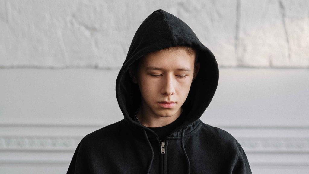 Грустный подросток в черной толстовке