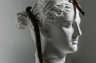 Каменная статуя греческой богини на которой ползает змея