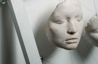Каменные маски висят на белой стене