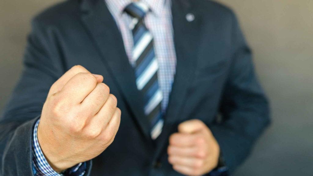 Мужчина в пиджаке показывает кулак