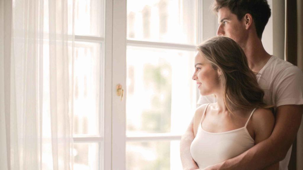 Парень и девушка обнимаются и смотрят в окно