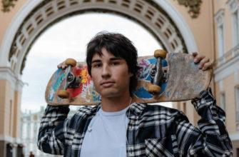 Парень со скейтом стоит на дворцовой площади