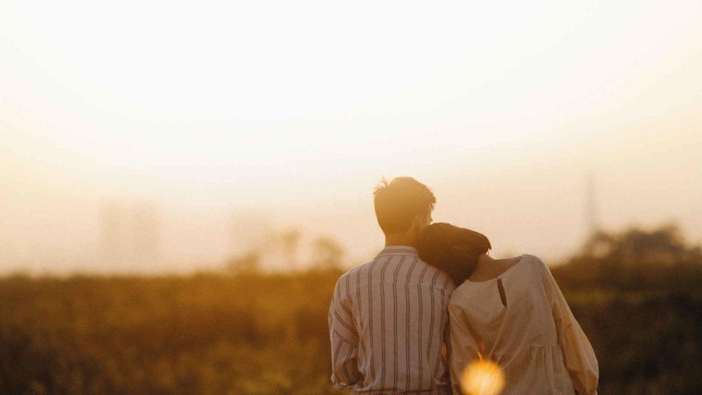 Счастливая пара смотрит закат в поле