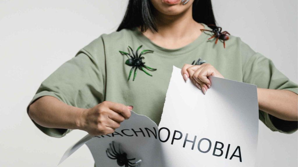 Женщина разрывает надись арахнофобия