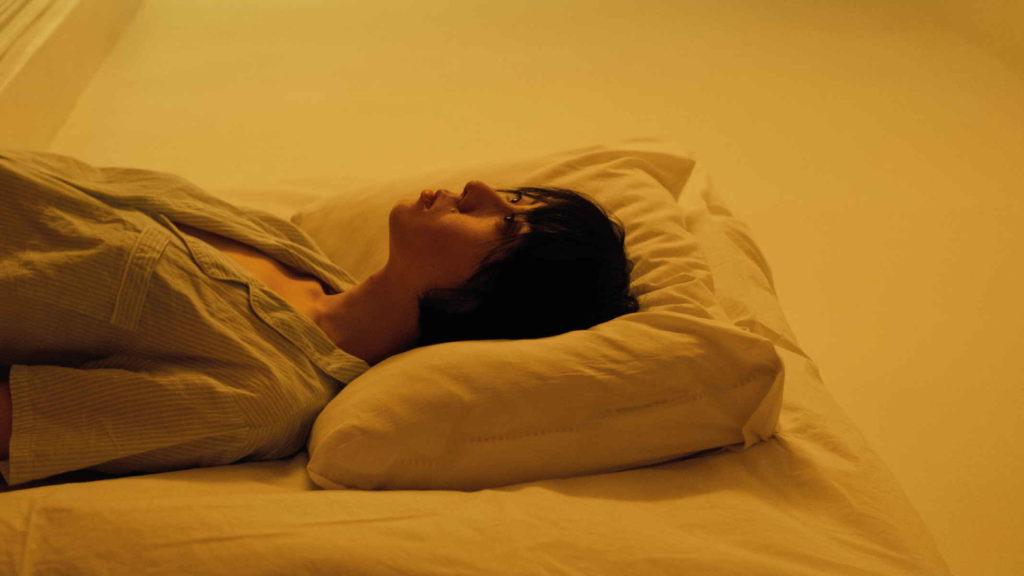 Женщина в желтой комнате лежит на подушке
